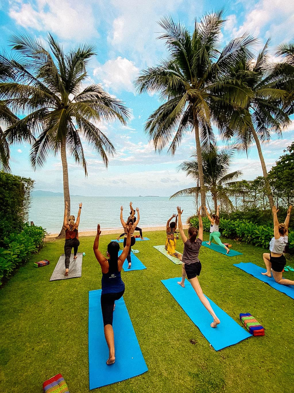 a G Adventures group doing yoga by the beach, wellness tourism
