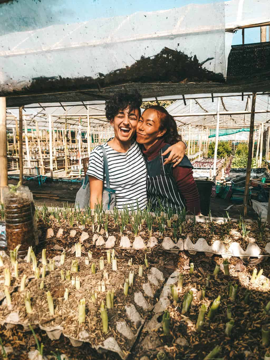 two happy woman with their arms around each other in front of some young plants
