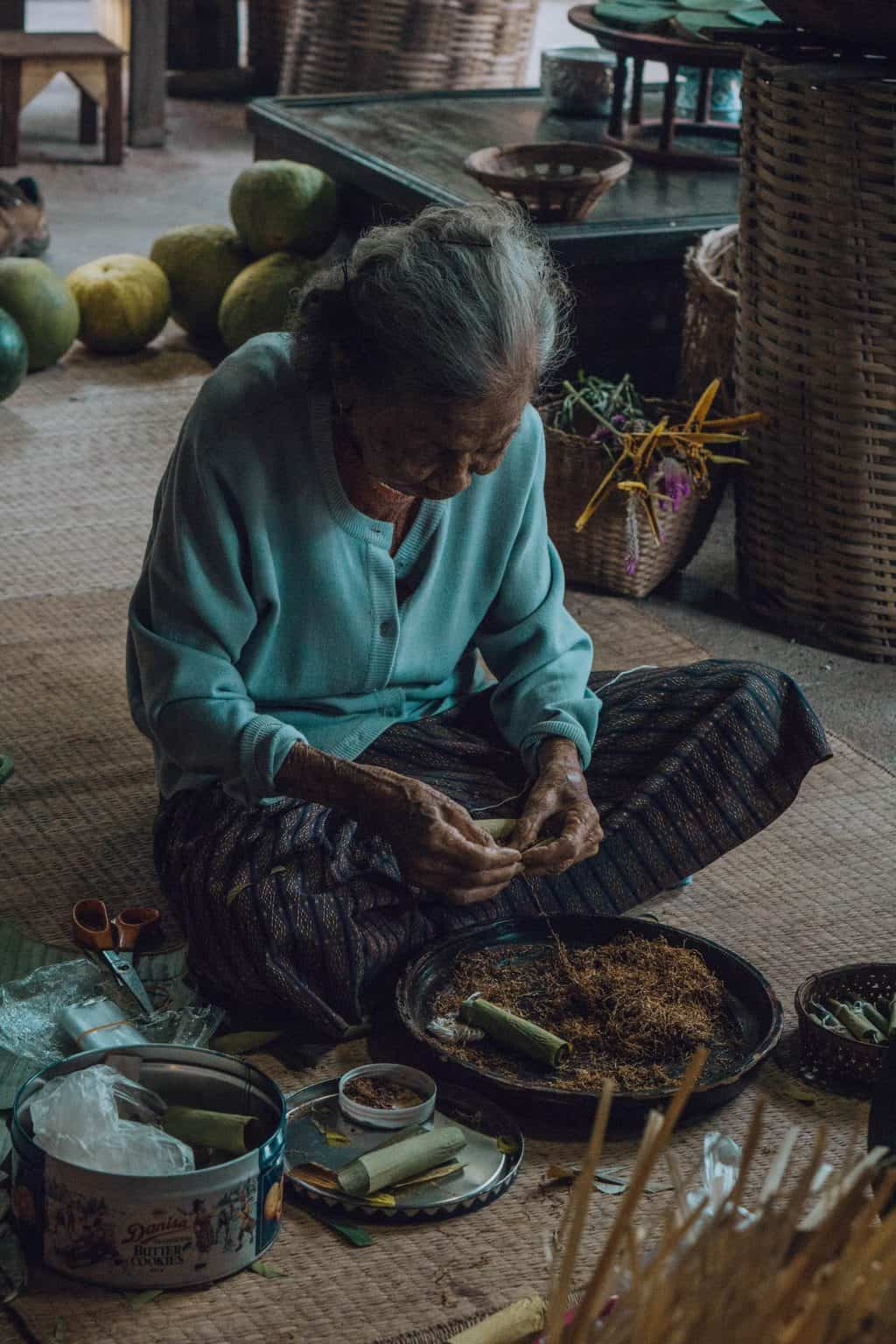 an elderly woman sitting on the floor hand rolling cigars, planning a trip to thailand