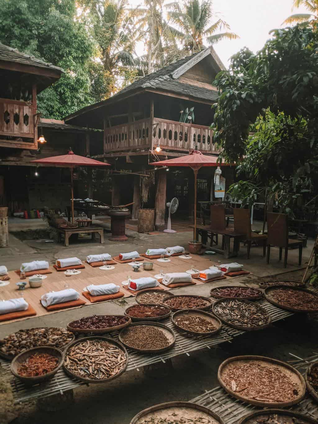 an outdoor dining area where guests sit on cushions on the floor, planning a trip to thailand