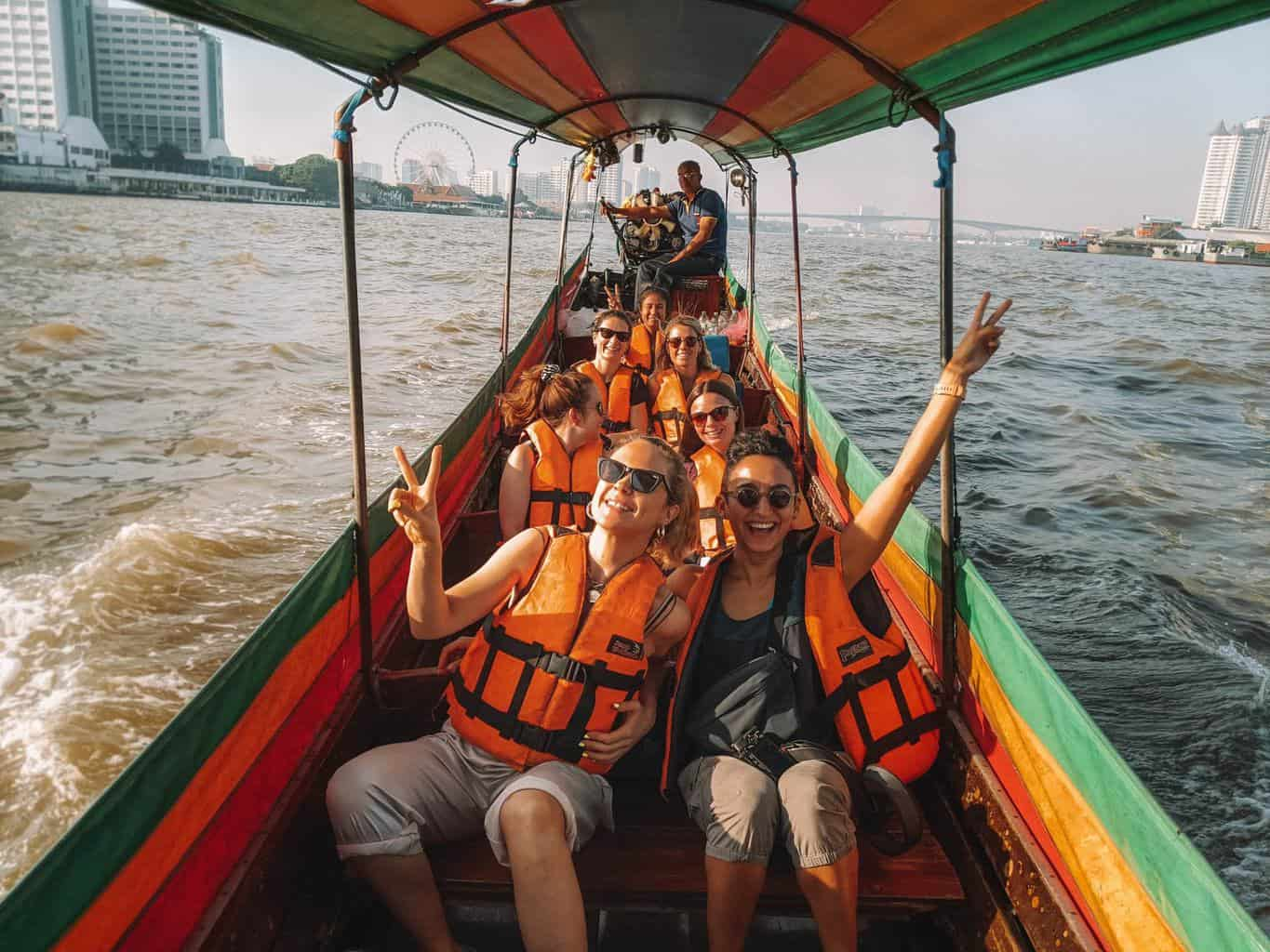 a happy G Adventures group in a long boat on a river