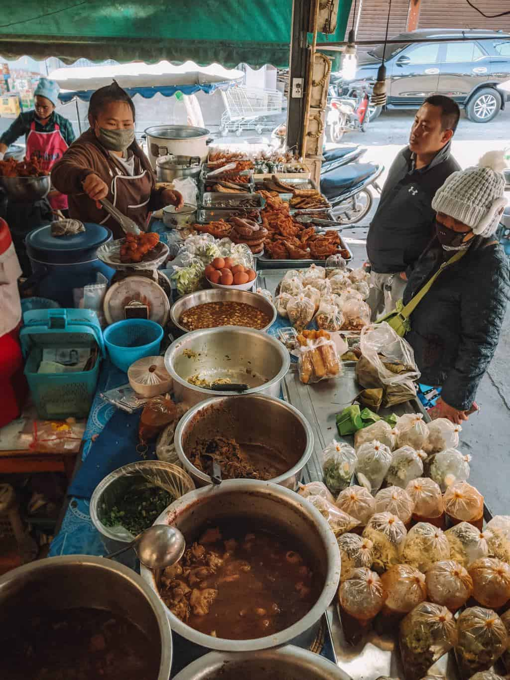 a Thai market stall selling food to take away, planning a trip to thailand
