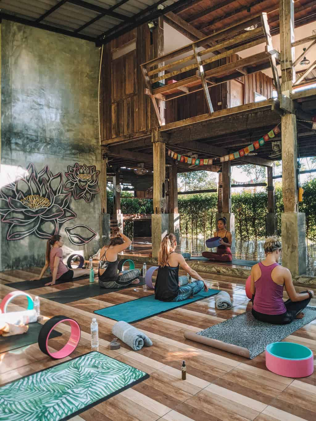 a G Adventures group sitting on yoga mats waiting to begin a yoga lesson in a contemporary yoga studio, wellness tourism