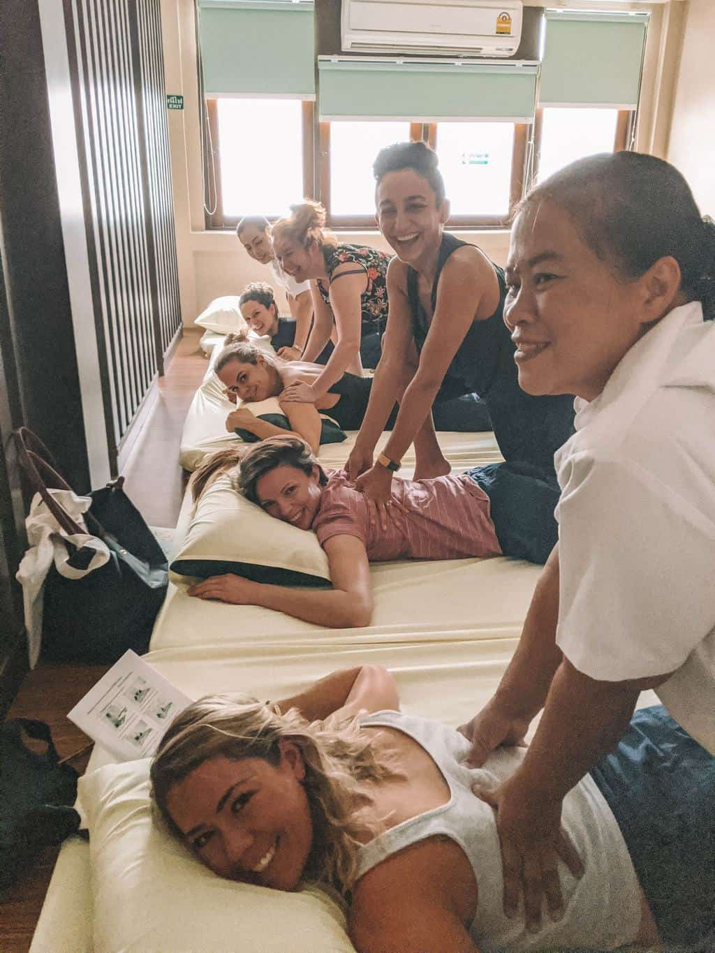 a G Adventures group giving each other Thai massages, wellness tourism