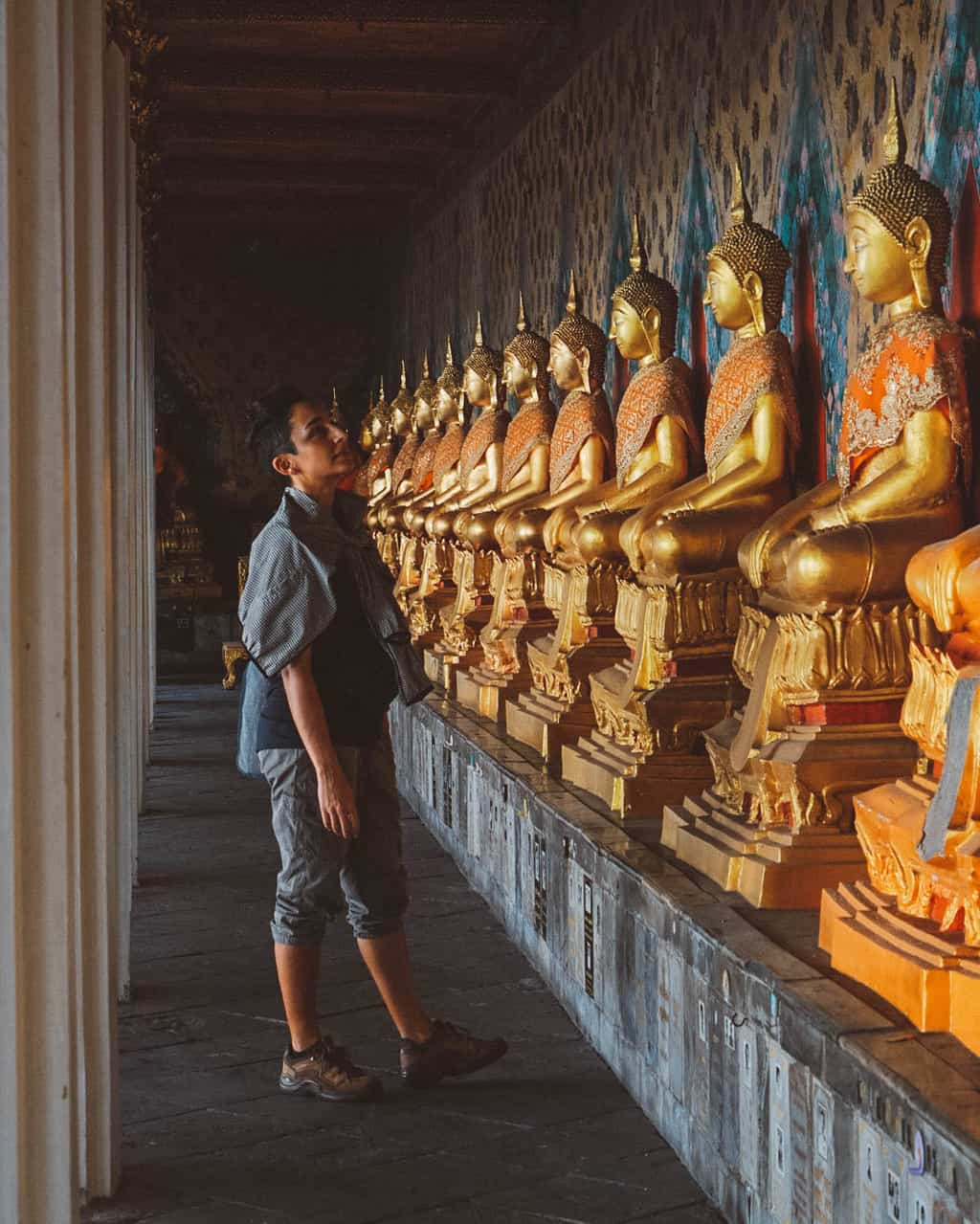 a woman standing in front of a row of golden Buddhas, planning a trip to thailand