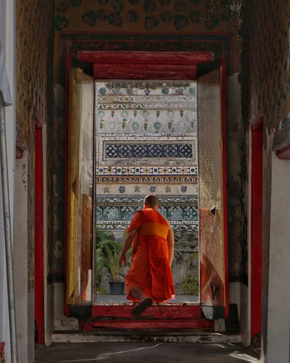 a monk in an orange robe walking through the doorway of a temple, planning a trip to thailand