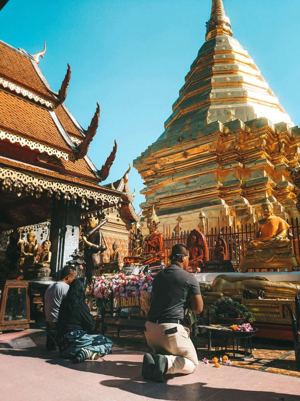 some people kneel in prayer before a golden structure in a temple, planning a trip to thailand