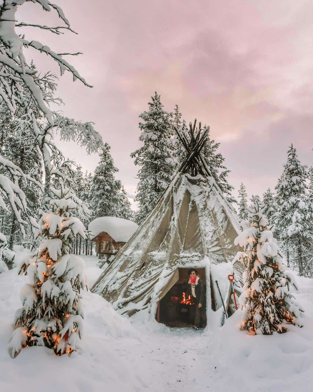 a girl stepping out of a snow covered teepee Finnish Lapland, Lapland destinations, Lapland Finland, Inghams