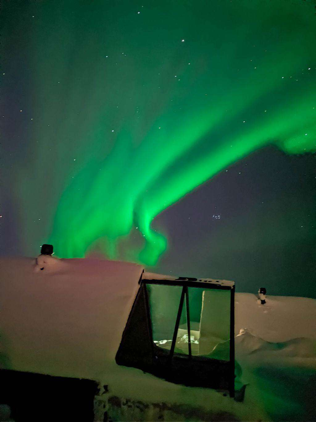 the green swirl of the Northern Lights above a building Finnish Lapland, Lapland destinations, Lapland Finland, Inghams