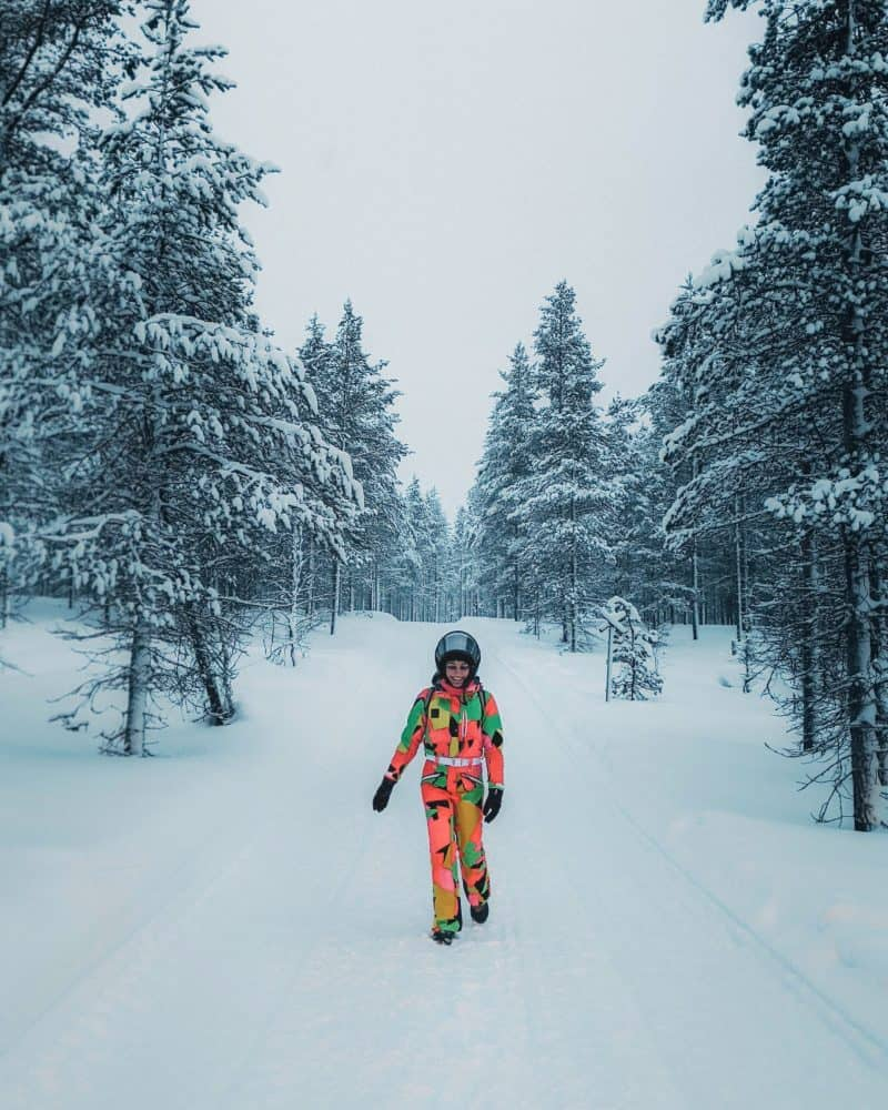 a woman in colourful winter gear walking in a snowy forest Finnish Lapland, Lapland destinations, Lapland Finland, Inghams