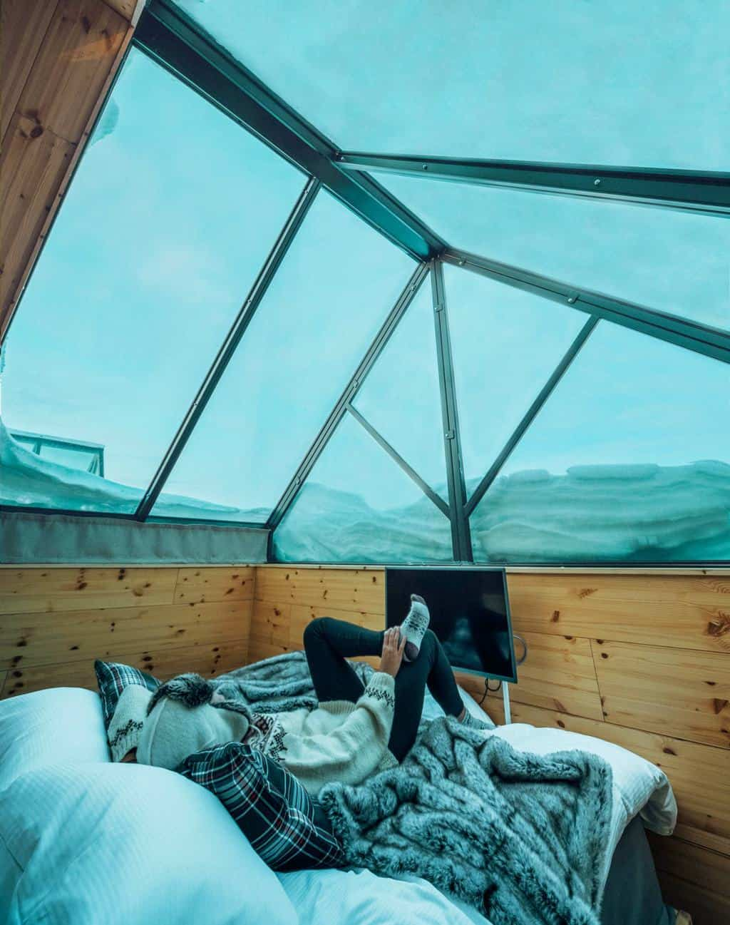 A woman lying on a bed looking up at the glass roofed cabin Finnish Lapland, Lapland destinations, Lapland Finland, Inghams