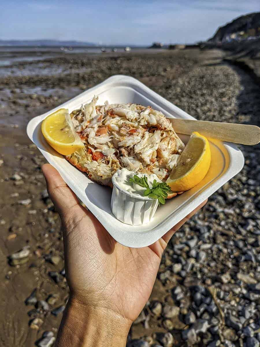 A takeaway box of dressed crab served in its shell with slices of lemon