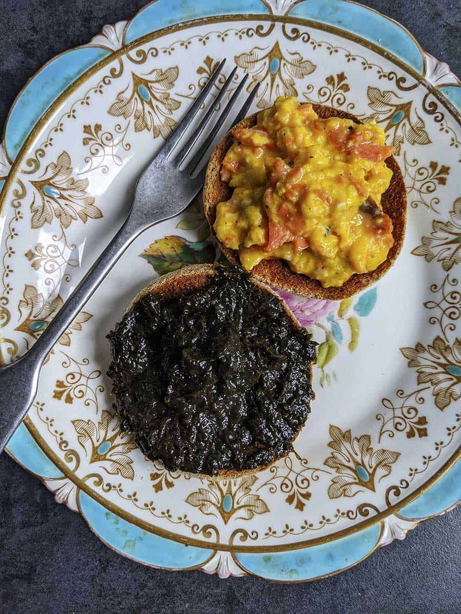 A plate with two muffins, one with scrambled eggs and one with laverbread