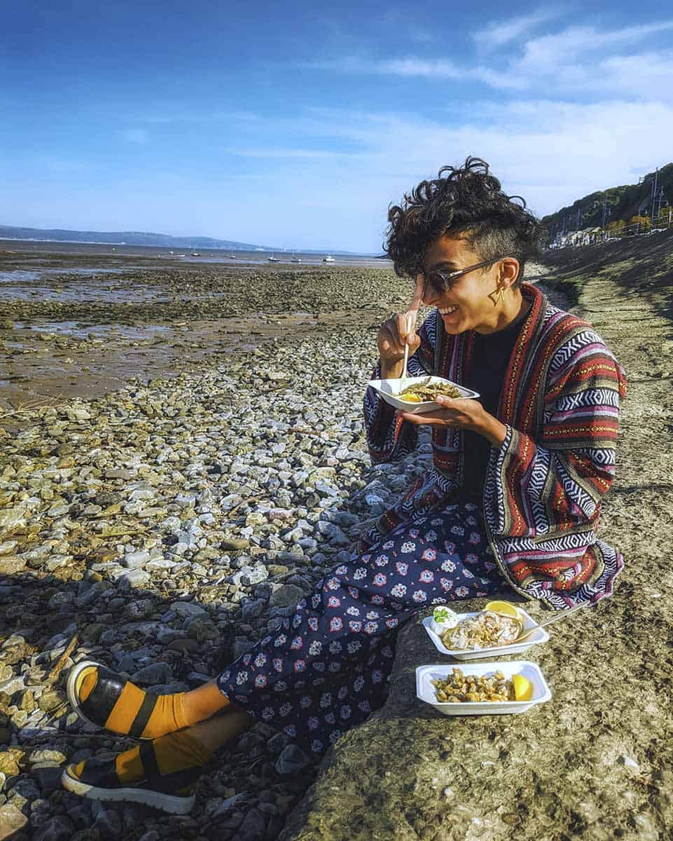 A girl sitting on a pebble beach eating takeaway seafood