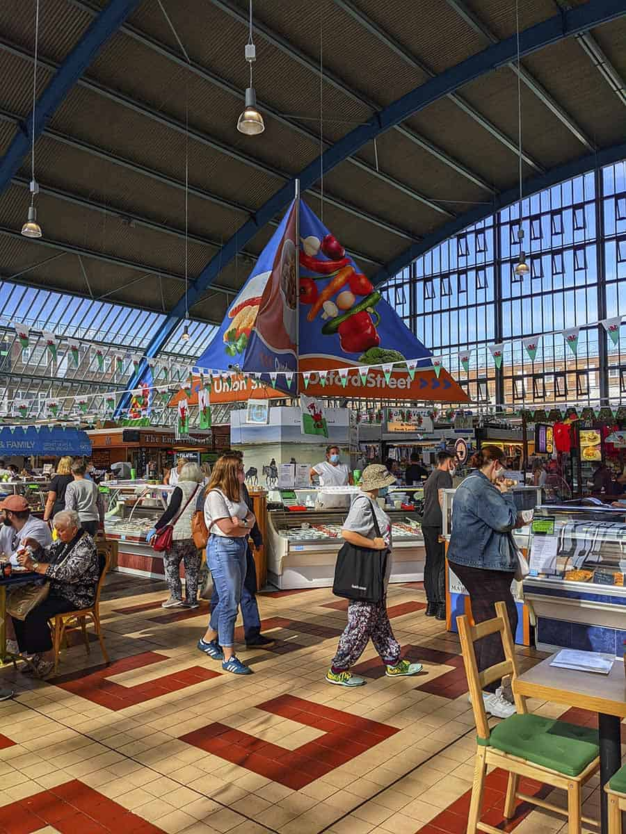 The inside of a spacious and colourful indoor market with large windows, stalls and people