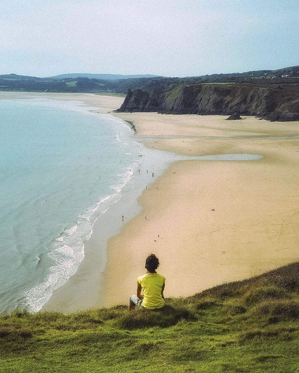A girl sitting on a grass mound on a clifftop looking out over a beautiful beach
