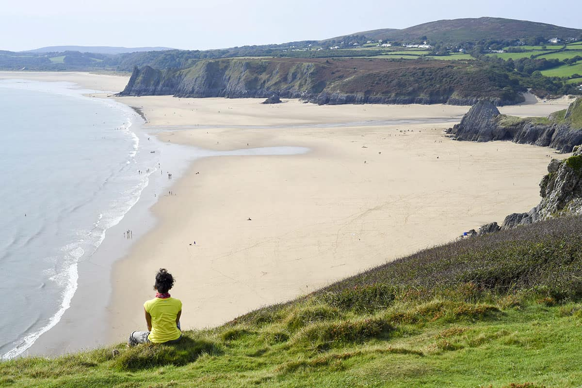 A woman in a yellow top on a grassy cliff top bank looking out over Three Cliffs Bay in Gower, Wales