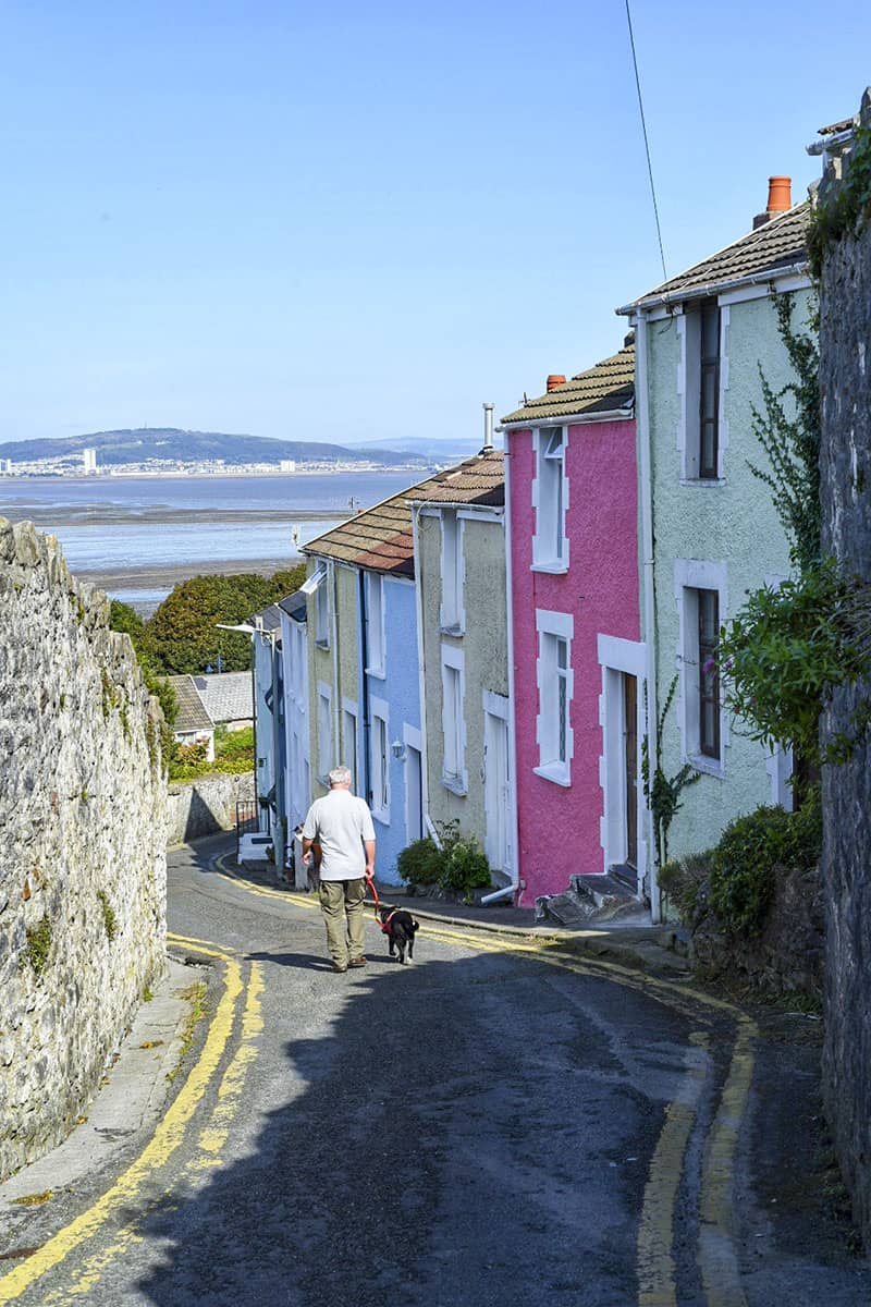 A man walking a dog down a steep lane lined with colourful pastel houses