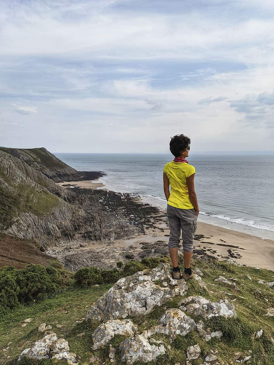 A girl standing on top of a cliff looking out to sea