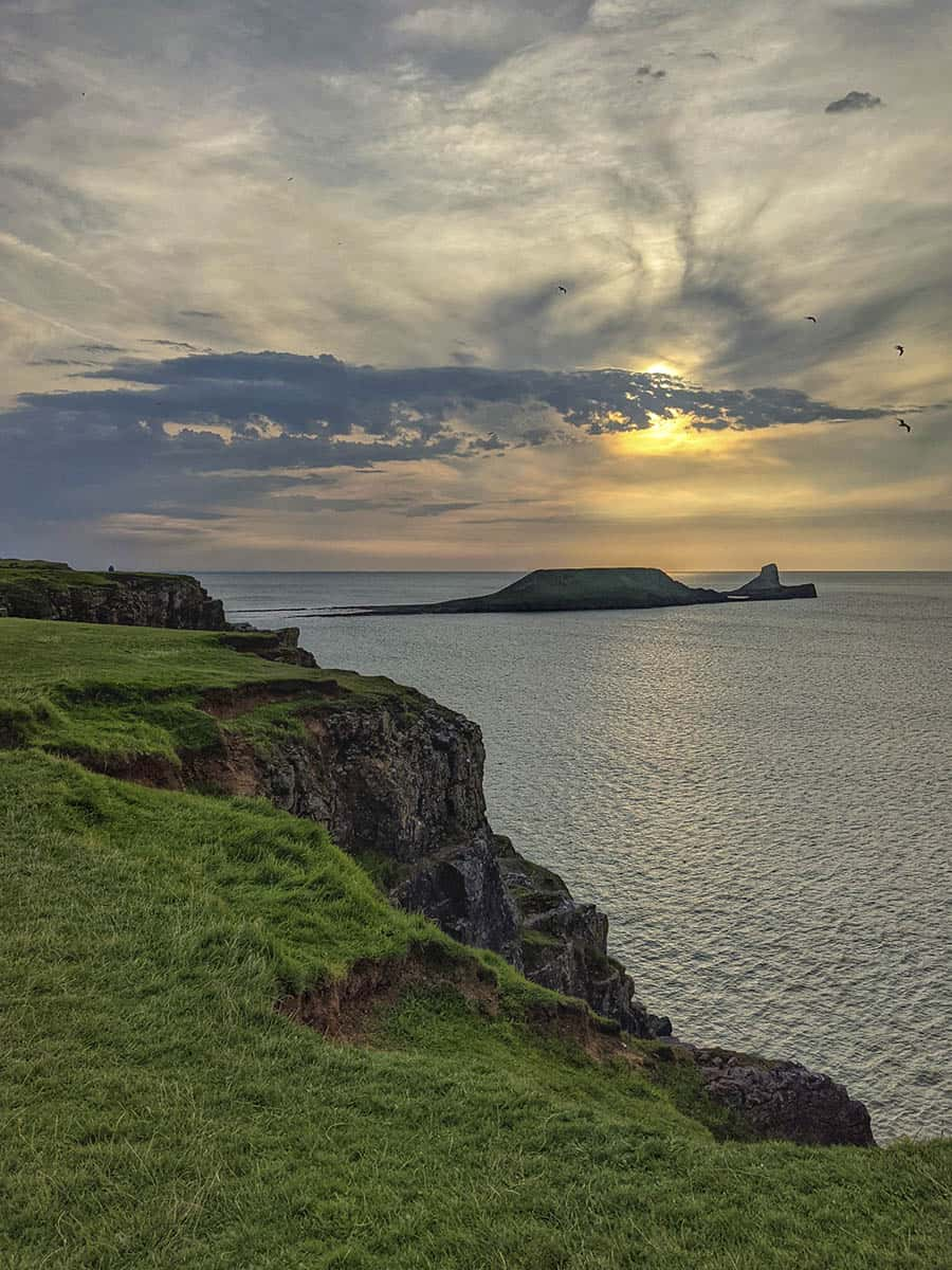 Grass covered cliff tops and the sea at sunset