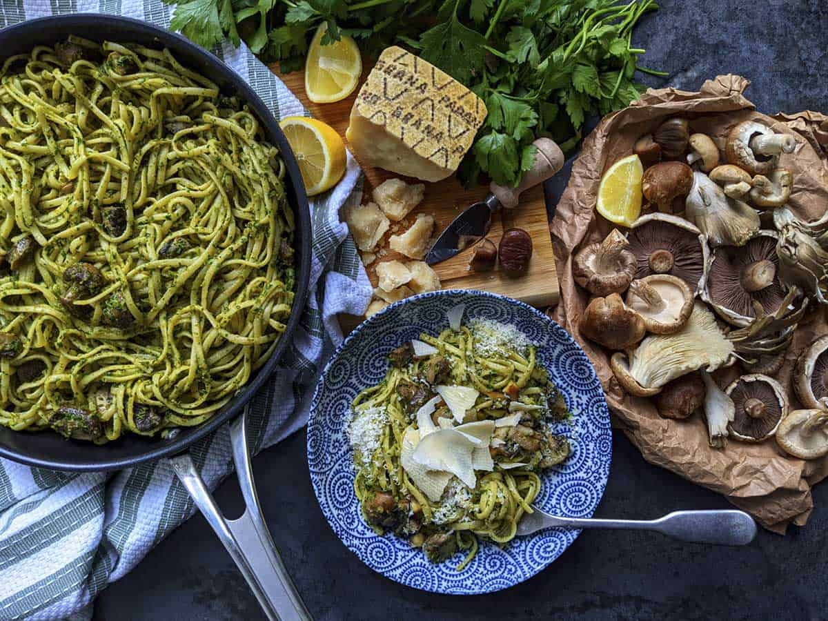 A frying pan full of a just-cooked pasta dish, alongside a bowl of plated up pasta and the raw ingredients within the dish, including Grana Padano cheese, mushrooms, lemon, parsley and chestnuts.