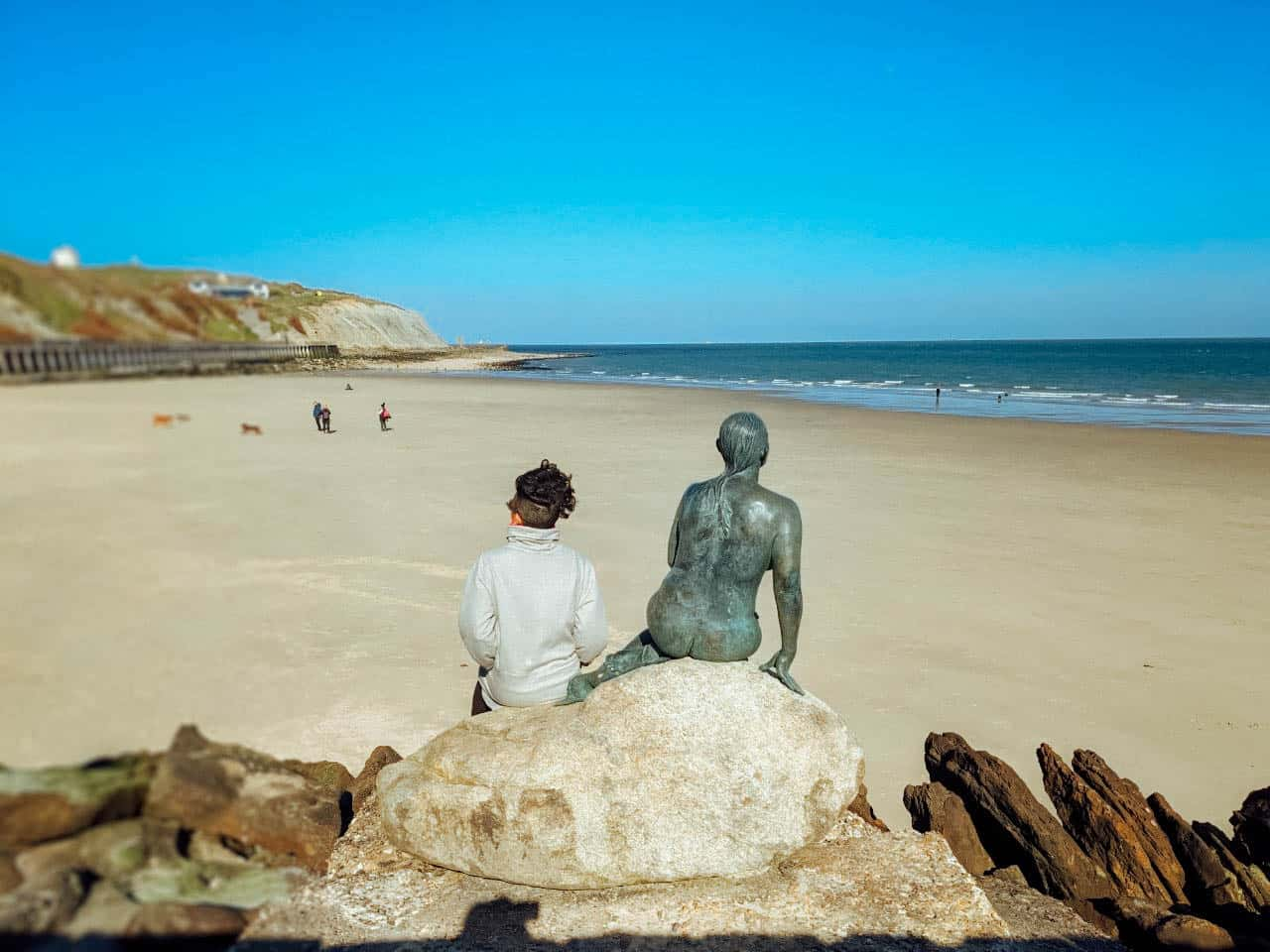 A girl sitting on a rock next to a sulpture of a naked woman, both looking out over a sandy beach towards the sea under a blue sky