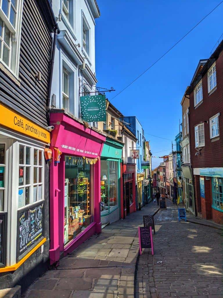 A view down a narrow cobbled street lined with colourful independent shop and restaurant fronts with chalk boards out the fronts under a blue sky