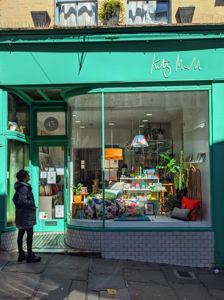 A vibrant mint green shopfront with a girl looking through the window at the colourful homeware items on display