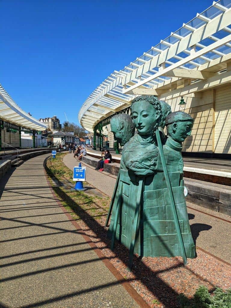 A five-headed sculpture, its body wrapped in blankets and cardboard, appears stranded and forlorn in the middle of the rail tracks at a disused and restored railway stationlorn