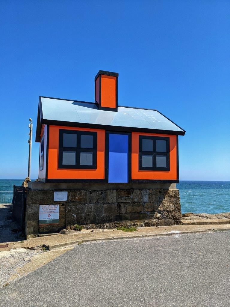 A mock house, one third of the size of a real house, of bright orange with a bright blue door against the background of a blue sea