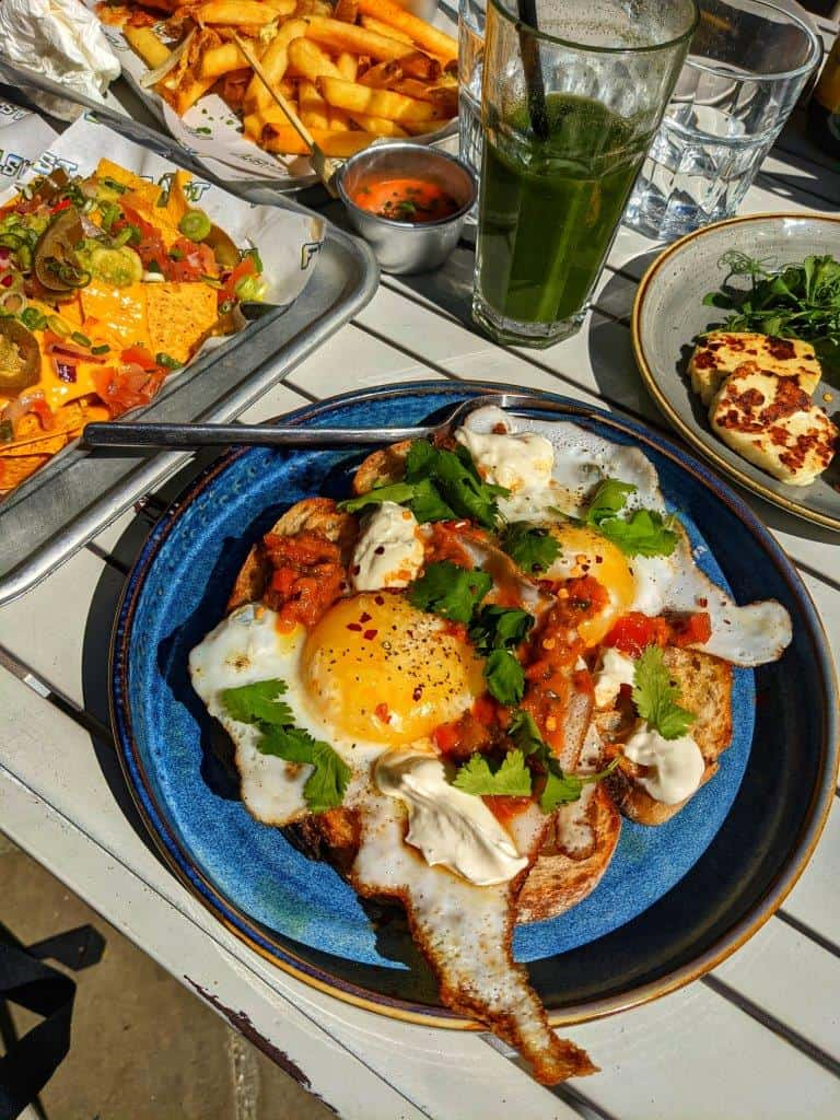 A restaurant dish of two large duck eggs on sourdough toast topped with coriander and tomato chutney, with a side of grilled halloumi, next to a loaded plate of nachos