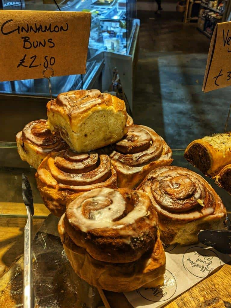 A stack of seven large and fluffy iced cinnamon buns on display in a bakery