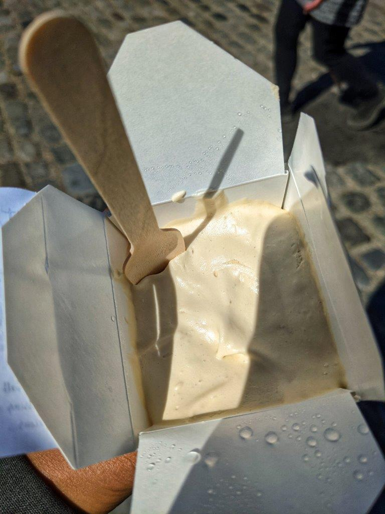 A small square cardboard container with the lid open to reveal ice cream inside with a wooden spoon sticking out the top
