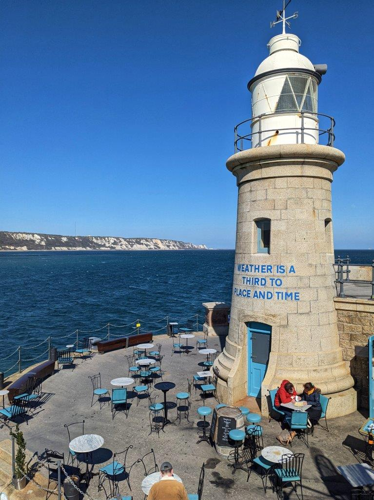 A small lighthouse on the end of the harbour arm with seats around its entrance and blue sea and skies in the background