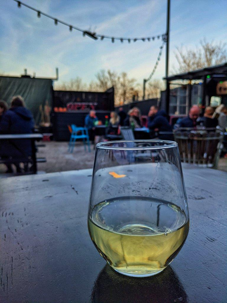 A glass of wine set on a table outside against a backdrop of patrons sitting at their own tables under at dusk