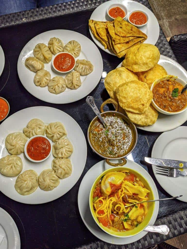 A delicious restaurant spread of various Nepalese dishes including daal, dumplings and noodle soup