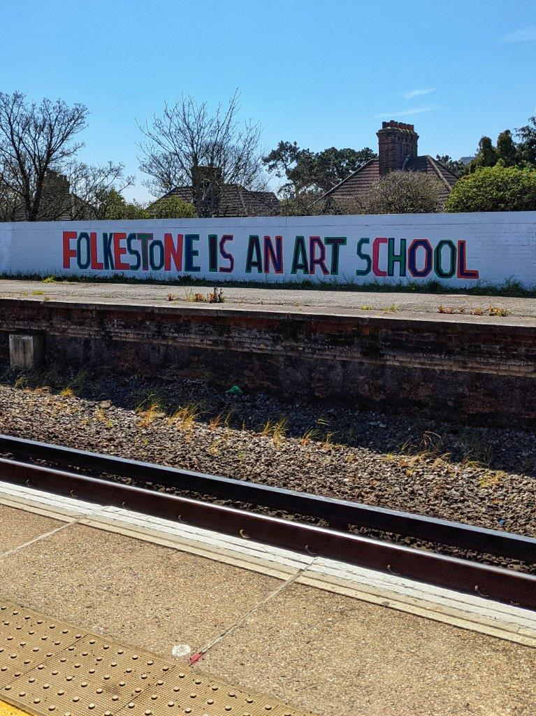 The words 'Folkestone Is An Art School' in large letters painted onto the side of a wall running the length of some railway tracks