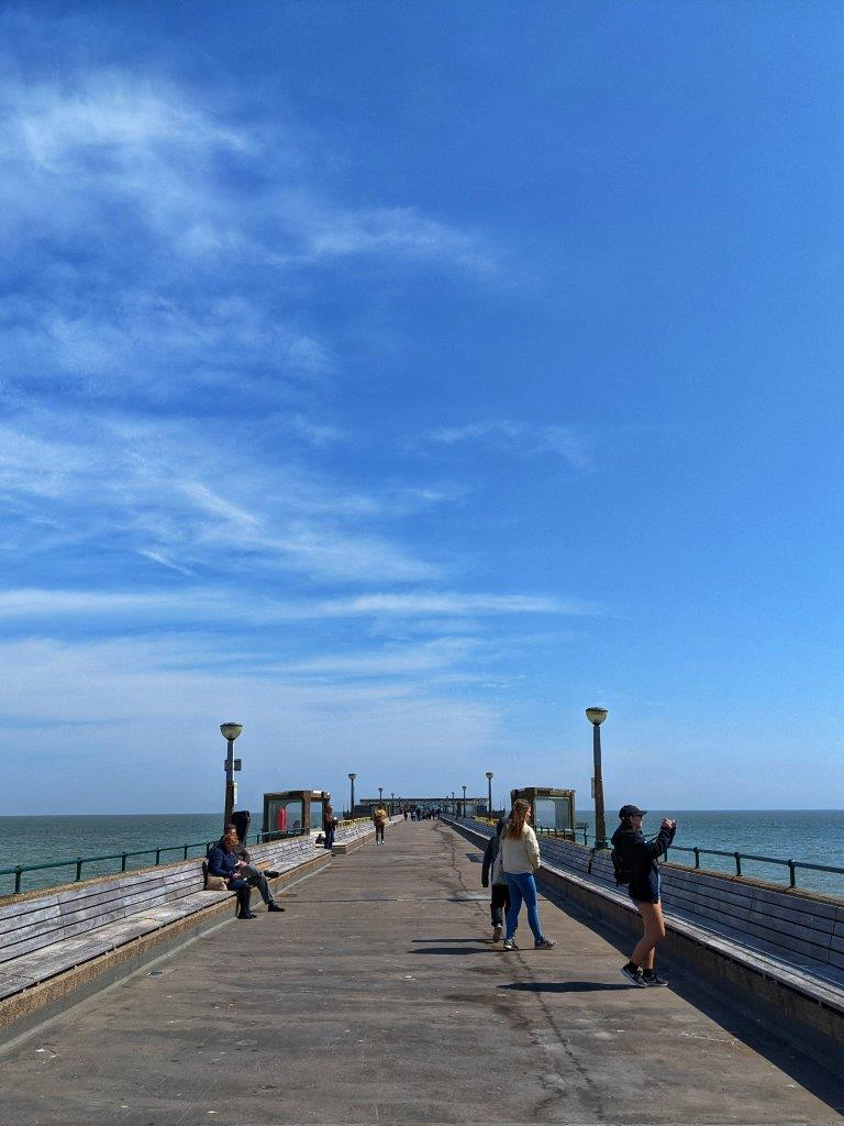 Lots of blue sky and a view looking down a pier with a few people walking along, the sea in the distance