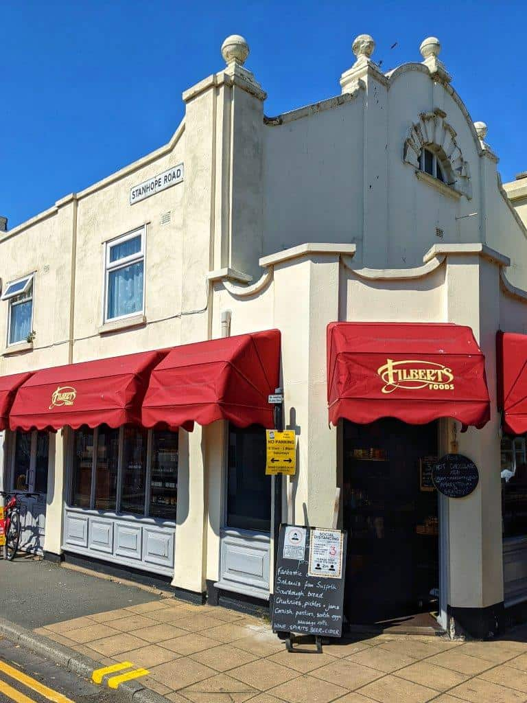 A corner view of a shop called 'Filberts Foods' with red awnings over the windows and white walls