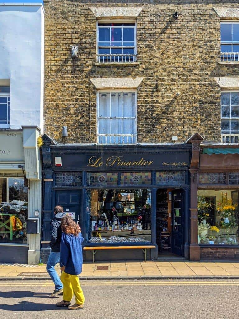 A handsome navy blue shop front called 'Le Pinardier' with bottles of wine in the window with two people looking in as they walk past