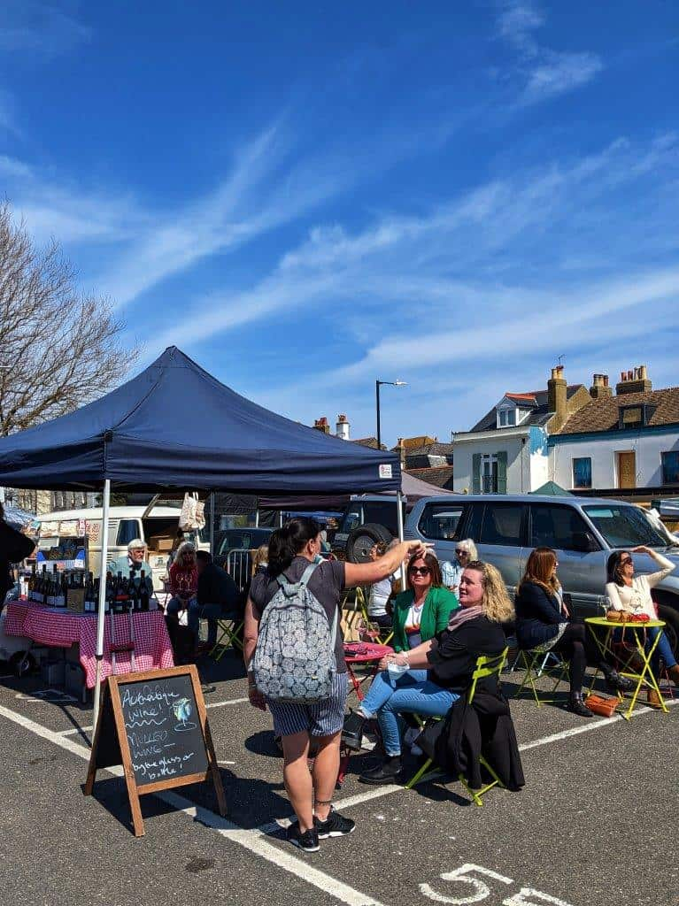 A gazeebo in a carpark under which there is a table laden with tine bottles, outside women sit on folding chairs enjoying their glasses of wine under a blue sky