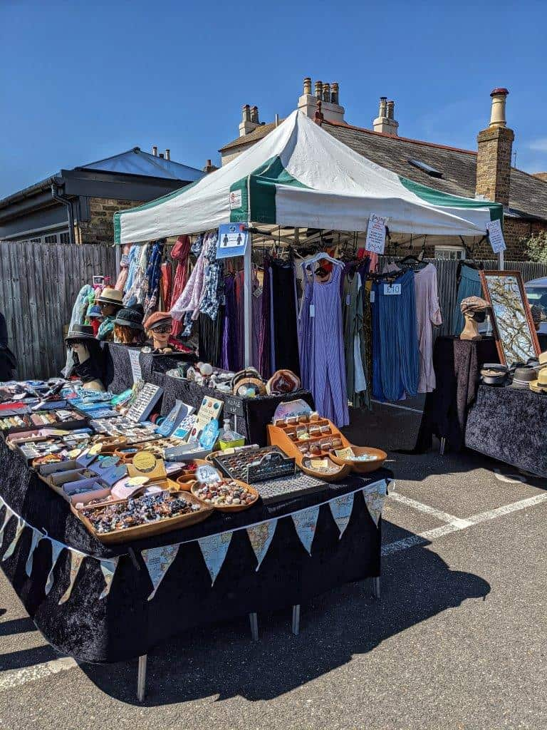 A vibrant market stall in a carpark with a table laden with trinkets and fully stocked clothing rails under a gazeebo
