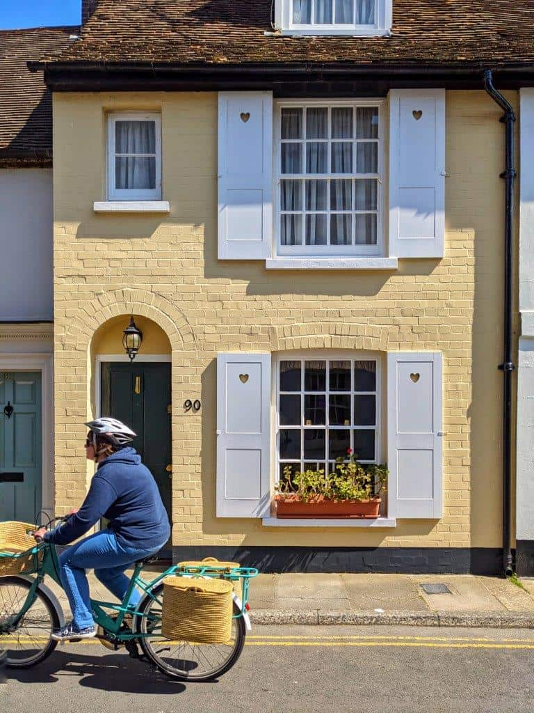 A buttercup yellow house front on with white window frames and shutters, a blue door and a person riding past it on a bicycle with baskets strapped to the back
