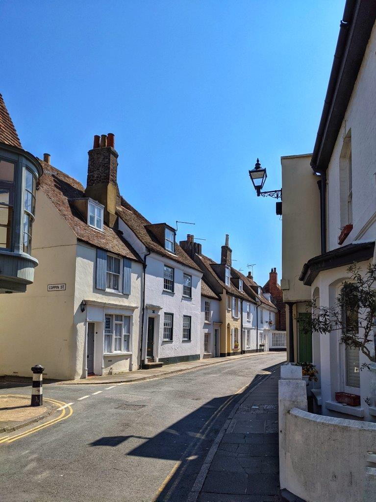 A view down a very picturesque residential street with old style houses and cottages on either side under a blue sky