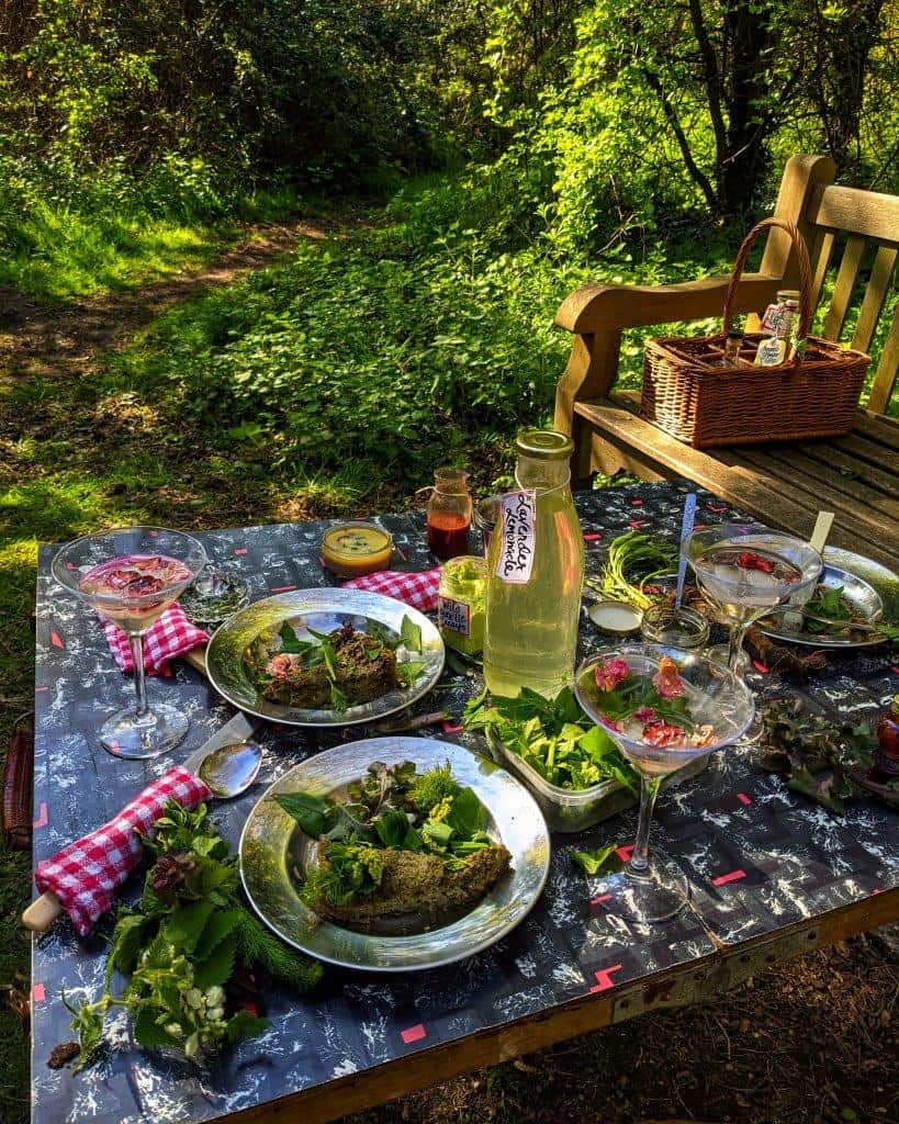 A bucolic picnic set-up laid out on a tressele table in a woodland clearing surrounded by foliage and a wooden bench, the table laden with springtime dishes, cutlery and drinks