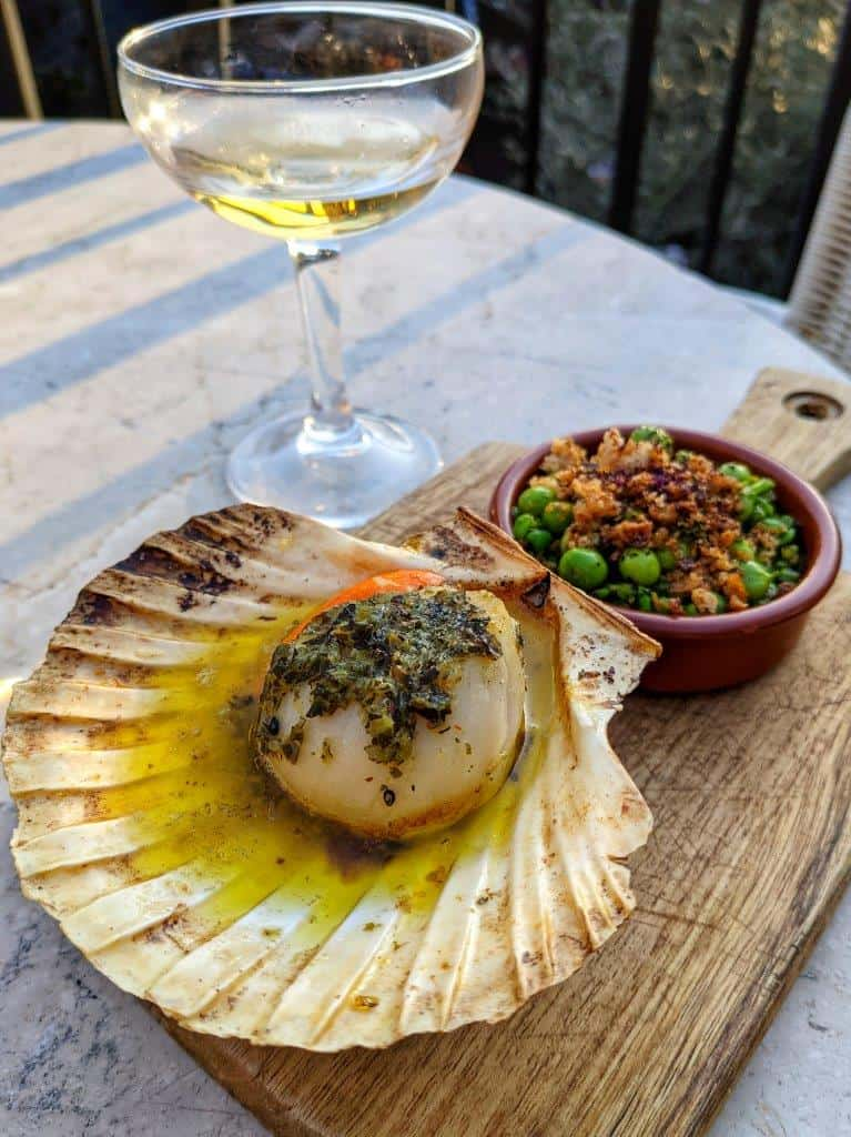 A restaurant dish of a cooked scallop served in its shell on a wooden board with a side of peas and a coupé glass of wine