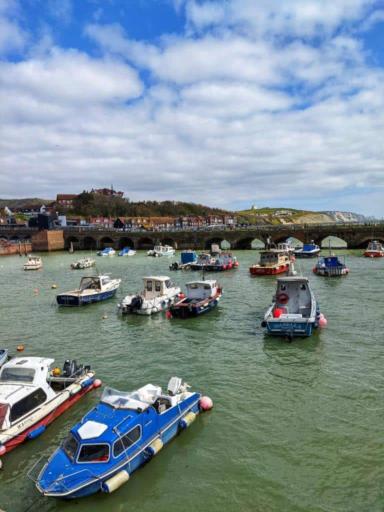 A harbour with small anchored fishing boats dotted about under a cloudy but bright sky