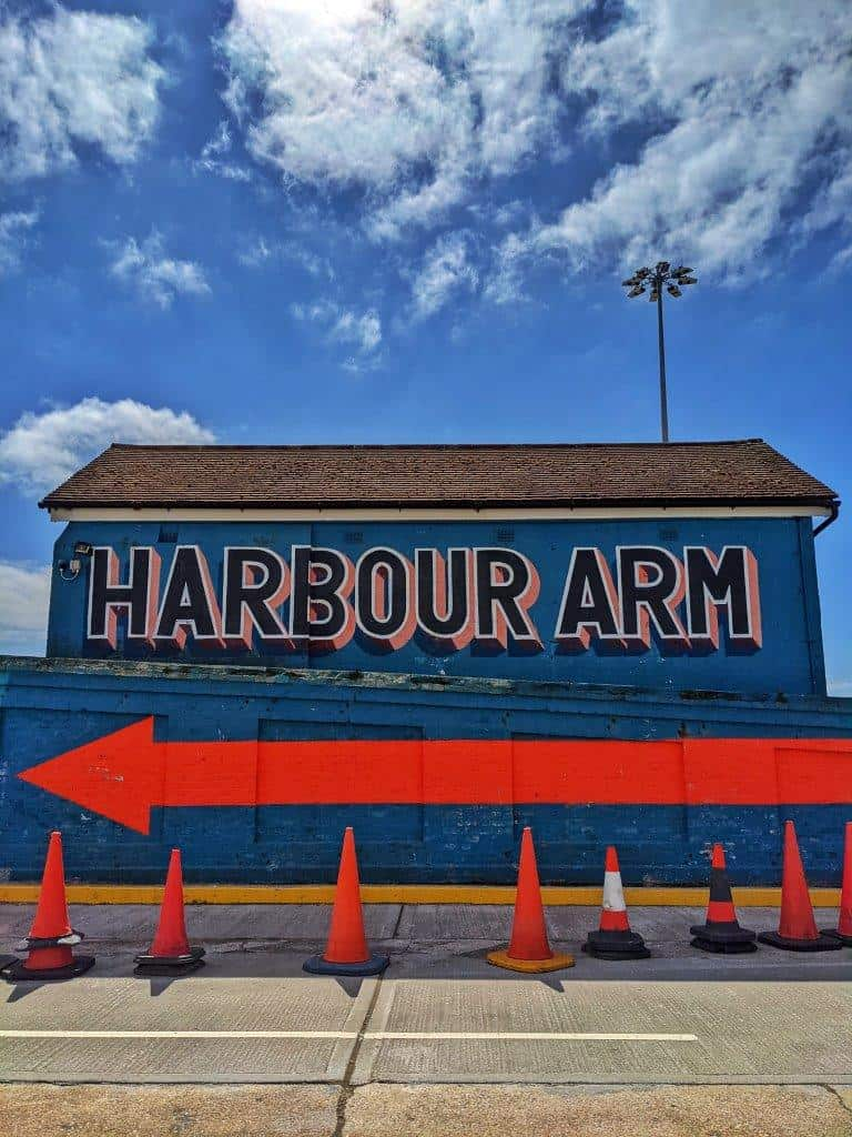 A small building painted blue with lettering that fills the whole of one wall reading 'Harbour Arm', underlined with a large red arrow pointing towards the left
