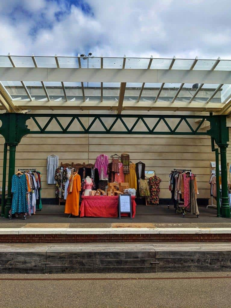 A colourful market stand on an ex-railway station platform displaying vintage clothing