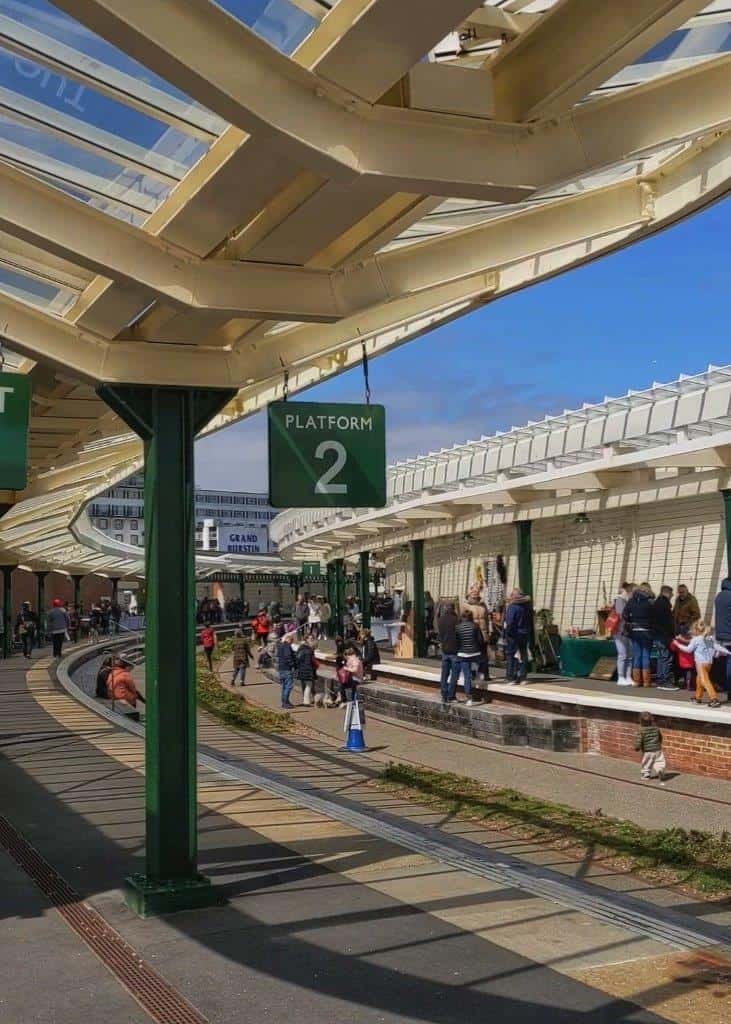 A restored ex-railway station showing the old rail tracks and platforms, now the location of a vibrant Sunday market